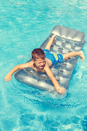 kids swimming: Little boy playing on air mattress in water