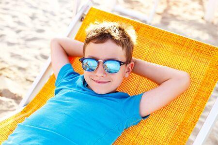 deckchair: Little boy relax on deckchair at beach