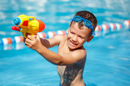 pistolas: Niño pequeño tiro con pistola de agua en la piscina