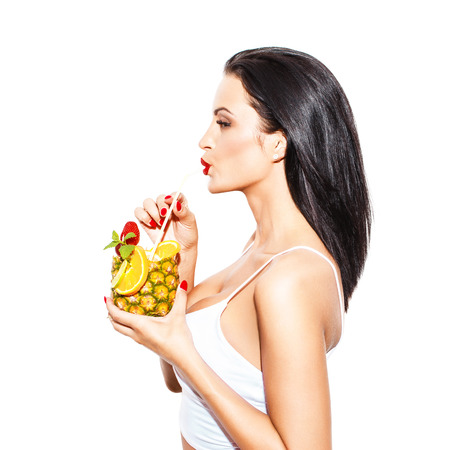 tropical drink: Woman drink tropical cocktail in pineapple with straw, isolated on white