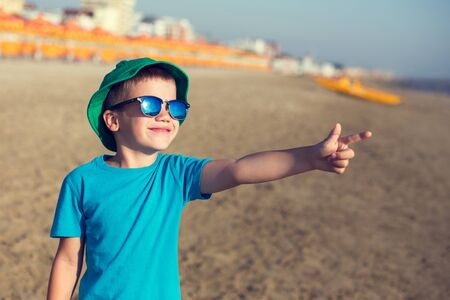 boy beautiful: Little boy showing away on beach, summer holiday Stock Photo