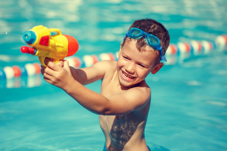 water gun: Little boy shooting with water gun in the pool, vintage style