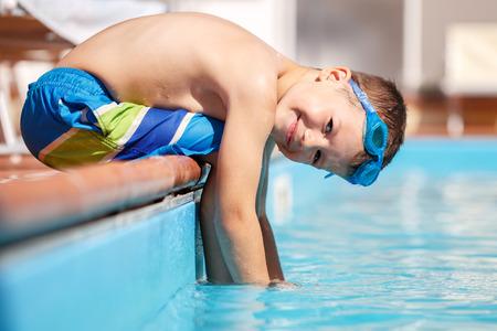 natacion: El niño pequeño se sienta en el borde de la piscina, vacaciones de verano Foto de archivo