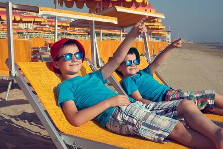 little boys: Little boys relax on deckchair showing away, summer holiday Stock Photo
