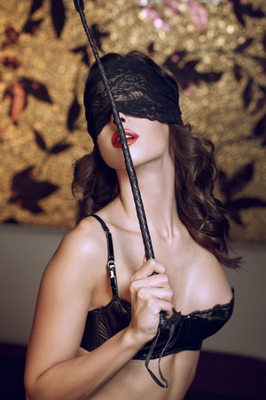 black sex: Sexy woman in lace eye cover holding whip, bdsm