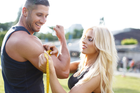 bodybuilding: Blonde woman measure mans biceps by yellow measuring tape in nature