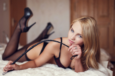 black sex: Sexy woman holding whip, lying on bed Stock Photo