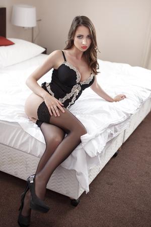 tetas: Mujer morena sexy con grandes tetas se sienta en la cama