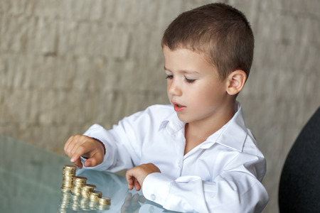 wealth concept: Little boy counting coins on glass desk in office Stock Photo