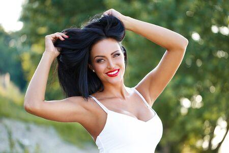 femme noire nue: Sexy femme brune jouant avec des cheveux plein air