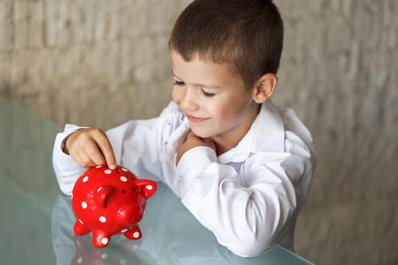 white piggy bank: Little boy insert coin into piggy bank in office