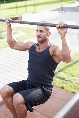 pullups: Man doing pull-ups on horizontal bar, outdoor workout