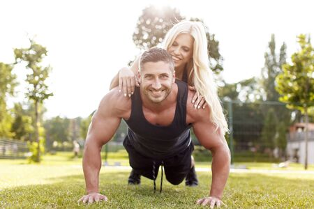 Man doing push-ups with woman on back, healthy couple, workout with own body weight, outdoor