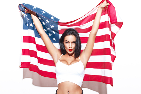 usa: Sexy brunette woman with USA flag posing at white wall