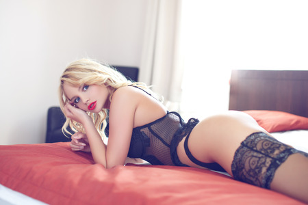 beautiful naked woman: Sexy blonde woman in underwear lying on bed, red lips