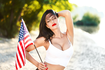 mujer morena atractiva que sostiene la bandera de EE.UU. al aire libre, los ojos cerrados