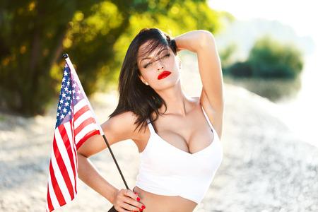 femme brune sexy: Sexy femme brune tenant USA flag en plein air, les yeux fermés Banque d'images