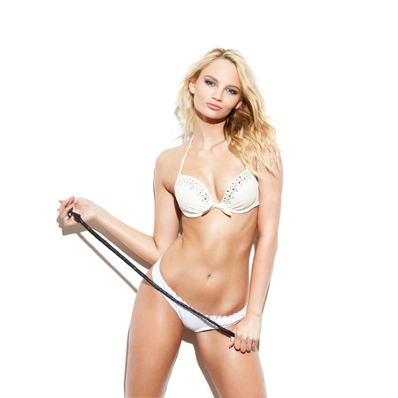 nude blonde girl: Sexy blonde woman with whip posing at white wall, bdsm