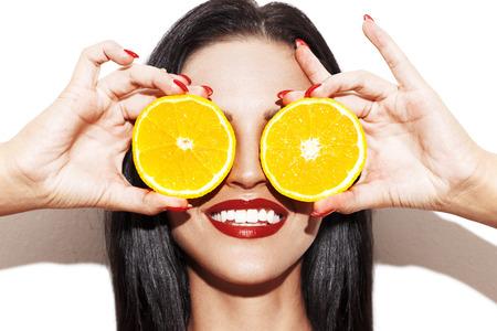 Brunette vrouw die oranje ringen aan de ogen