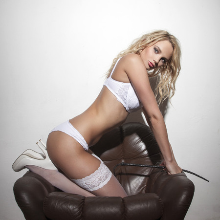 mujeres desnudas: Mujer rubia atractiva que presenta con el látigo en el sofá en la pared blanca