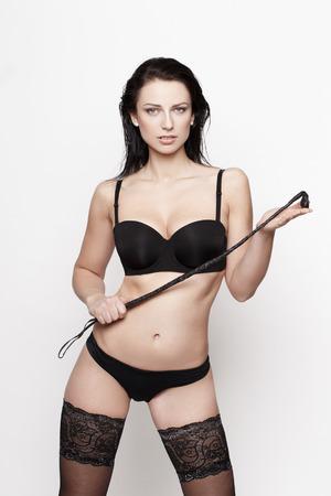 hot sex: Sexy brunette woman in black underwear holding whip, bdsm