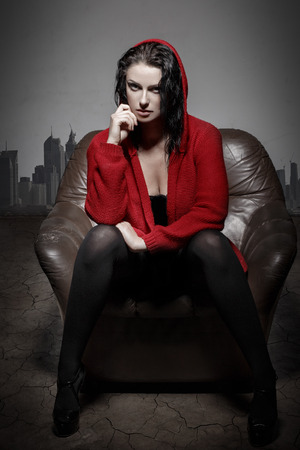 utopia: Sexy woman in desert sitting on sofa, utopia, global warming Stock Photo