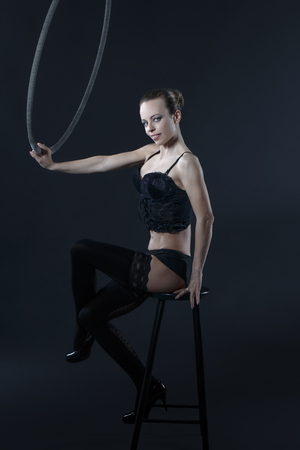 sexual girl: Sexy woman sit on stool with aerial hoop in studio