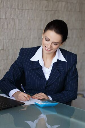 confide: Sussessful businesswoman writing and laughing in office
