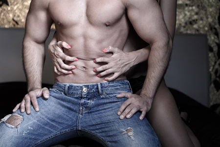 romantic sex: Woman grasps sexy macho mans abs at night