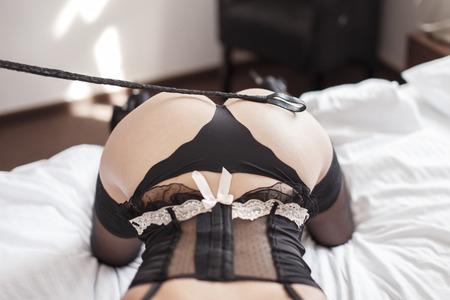 seks: Sexy vrouw met een zweep op ezel, bdsm Stockfoto