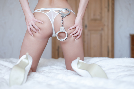 nude ass: Sexy woman ass in white panties with handcuffs on bed