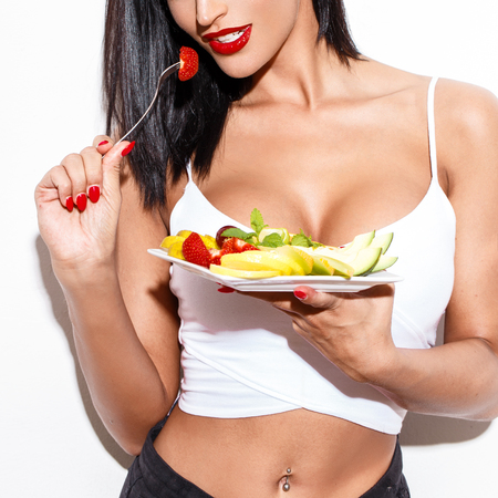 salad fork: Sexy woman eating fruit salad at white wall Stock Photo