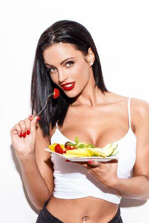 ensalada de frutas: Mujer que come la ensalada de fruta en la pared blanca