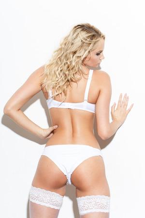 mujer rubia desnuda: Mujer rubia atractiva en ropa interior blanca que presenta en la pared