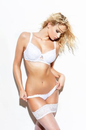 mujer rubia desnuda: Mujer rubia atractiva en ropa interior posando, aislado en blanco, sensualidad