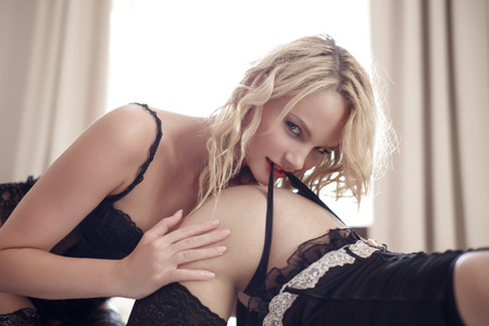 sexual nude: Sexy blonde woman bite lovers panties, lesbian foreplay Stock Photo