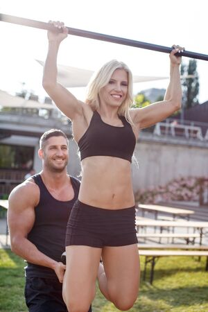 pull up: Man helps woman pull up on horizontal bar, outdoor Stock Photo