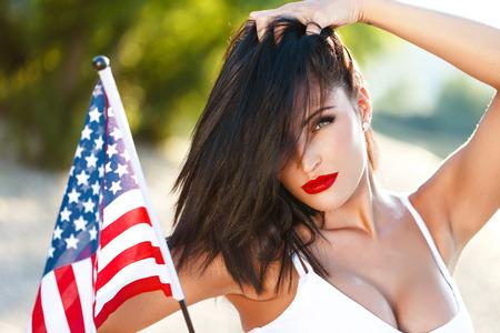red lips: mujer morena atractiva que sostiene la bandera de EE.UU. retrato al aire libre