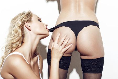 seks: Sexy lesbische blonde vrouw beet liefhebbers slipje op witte muur Stockfoto