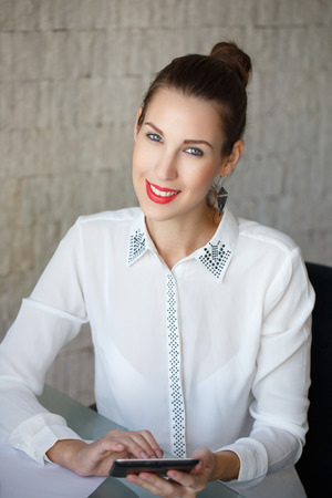 confide: Attractive businesswoman with tablet, red lips, in office