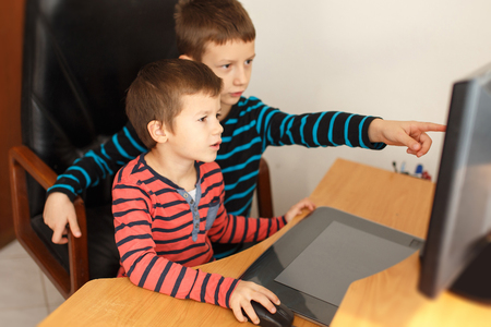 boy kid: Little boys learning at computer or playing game