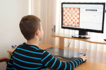 gamer: Little boy play online chess, little clever gamer at home