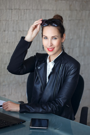 modern businesswoman: Modern confident businesswoman in office after work in leather jacket Stock Photo