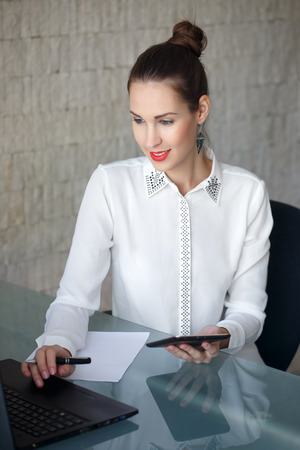 modern businesswoman: Modern businesswoman typing on laptop, red lips, in office