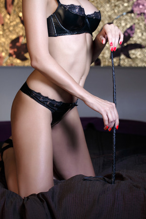 black sex: Sexy dominatrix body with whip on bed in luxury bedroom, bdsm Stock Photo