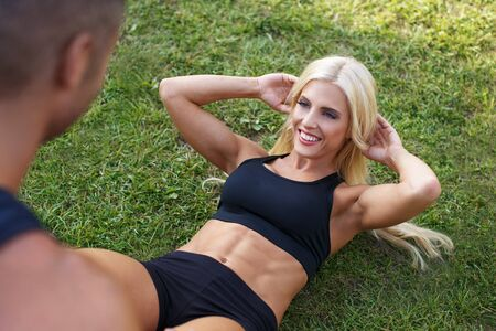 situp: Blonde fit woman doing sit-up with with personal trainer, healthy lifestyle