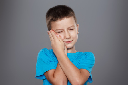 erosion: Little boy with toothache on grey background