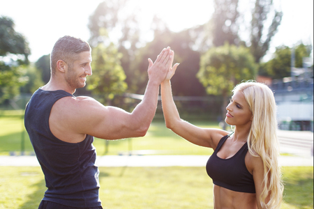after: Blonde woman with personal trainer after workout, teamwork, give high five