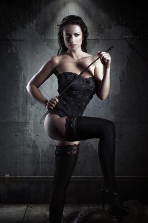 sexuales: Mujer atractiva con el látigo en la localización industrial, el cabello y el cuerpo mojado, bdsm