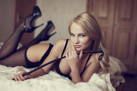 sex: Mujer rubia atractiva sosteniendo el látigo en la cama, bdsm Foto de archivo